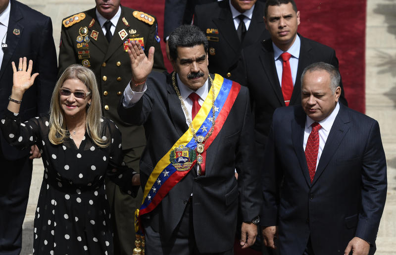 Venezuela's President Nicolas Maduro, center, first lady Cilia Flores, left, and Constituent Assembly President Diosdado Cabello arrive to the grounds of the National Assembly where Maduro will give his annual address to the nation inside the Constituent Assembly in Caracas, Venezuela, Tuesday, Jan. 14, 2020. (AP Photo/Matias Delacroix)