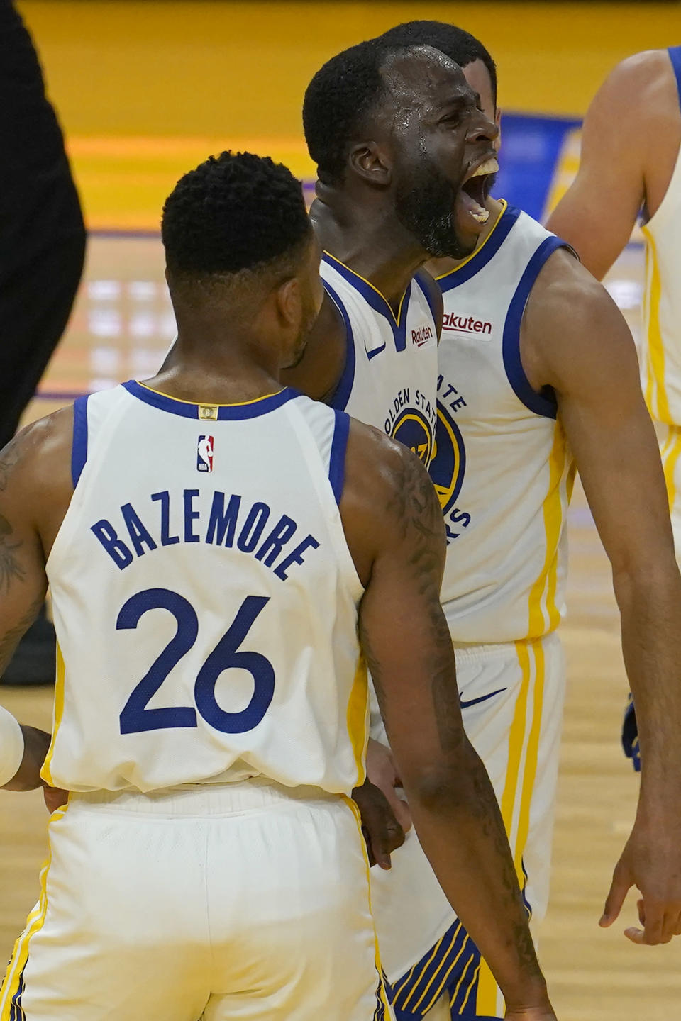 Golden State Warriors forward Draymond Green, middle, reacts between forward Kent Bazemore (26) and guard Mychal Mulder after a Memphis Grizzlies foul during the first half of an NBA basketball game in San Francisco, Sunday, May 16, 2021. (AP Photo/Jeff Chiu)