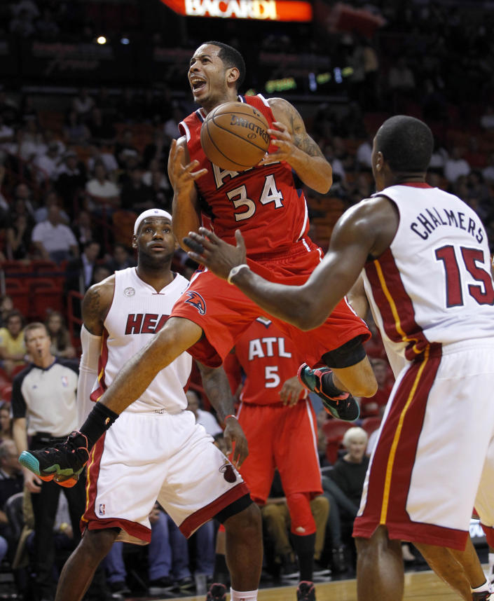 Atlanta Hawks' Devin Harris (34) goes to the basket between Miami Heat's Mario Chalmers (15) and LeBron James, background, during the first half of an NBA basketball game, Monday, Dec, 10, 2012, in Miami. (AP Photo/Alan Diaz)