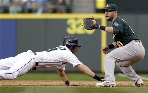 Seattle Mariners' Dustin Ackley, left, dives back to first on a pickoff-attempt as Oakland Athletics first baseman Daric Barton waits for the ball in the fifth inning of a baseball game on Saturday, May 11, 2013, in Seattle. (AP Photo/Elaine Thompson)