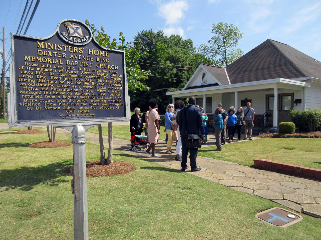 In this April 27, 2018 photo, a tour group gathers in Montgomery, Ala., on the street where Martin Luther King, Jr. lived from 1954-1960 while serving as minister of the Dexter Avenue King Memorial Baptist Church. During that time, King led the Montgomery bus boycott that was sparked by the arrest of Rosa Parks. That protest resulted in a U.S. Supreme Court ruling that segregation on public buses was unconstitutional. (AP Photo/Beth J. Harpaz)