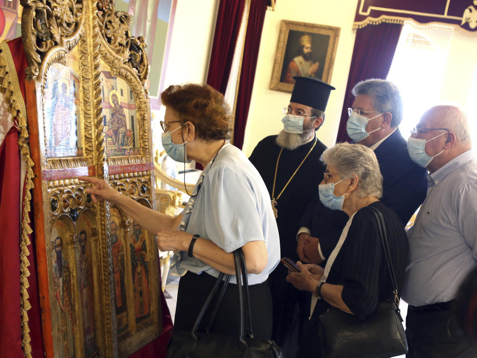 A cleric and others examine a pair of ornate, gilded doors that guard the altar of a church, at the Archbishopric in the capital Nicosia, Thursday, Sept. 16, 2021. The 18th century doors that were looted from the church of Saint Anastasios in the breakaway north of the ethnically divided island nation were repatriated from a Japanese art college after a long legal battle. (AP Photo/Philippos Christou)