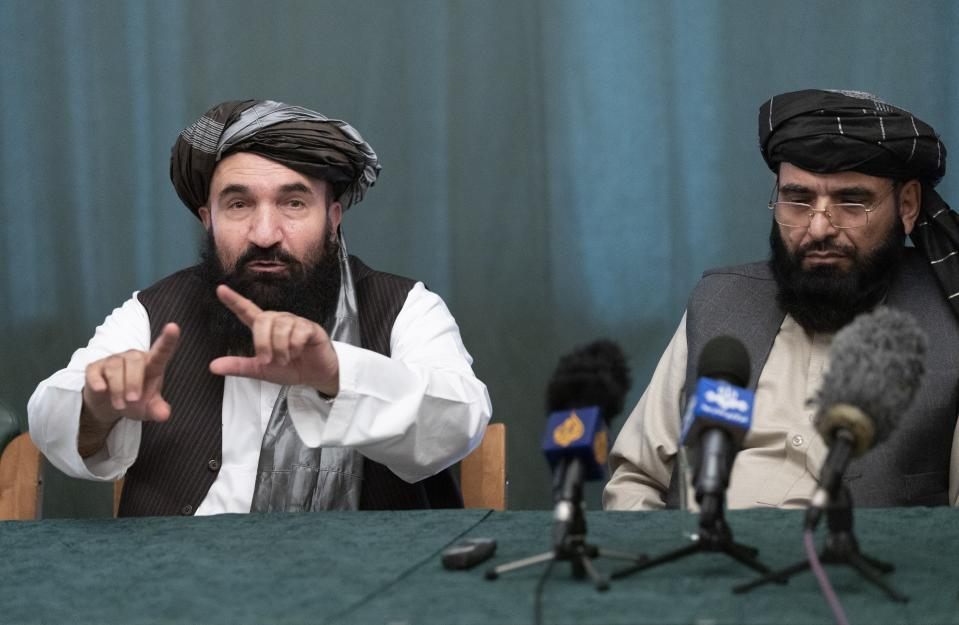"""Khairullah Khairkhwa, former western Herat Governor and one of five Taliban released from the U.S. prison on Guantanamo Bay in exchange for U.S. soldier Bowe Bergdahl, left, gestures while speaking as Suhail Shaheen, member of negotiation team listens to him during their joint news conference in Moscow, Russia, Friday, March 19, 2021. The Taliban warned Washington against defying a May 1 deadline for the withdrawal of American and NATO troops from Afghanistan promising a """"reaction"""". (AP Photo/Alexander Zemlianichenko, Pool)"""