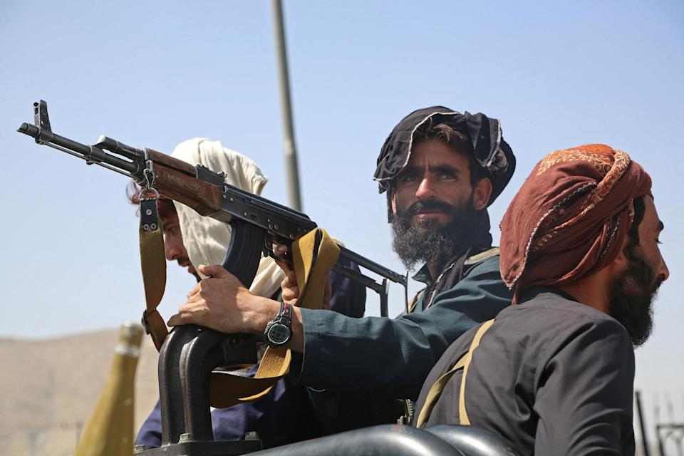 Taliban fighters stand guard in a vehicle along the roadside in Kabul on August 16, 2021, after a stunningly swift end to Afghanistan's 20-year war, as thousands of people mobbed the city's airport trying to flee the group's feared hardline brand of Islamist rule. (- /AFP via Getty Images)