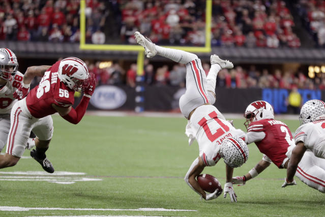 Ohio State wide receiver Chris Olave (17) is tackled by Wisconsin safety Reggie Pearson (2) as linebacker Zack Baun (56) watches during the second half of the Big Ten championship NCAA college football game Saturday, Dec. 7, 2019, in Indianapolis. (AP Photo/Michael Conroy)