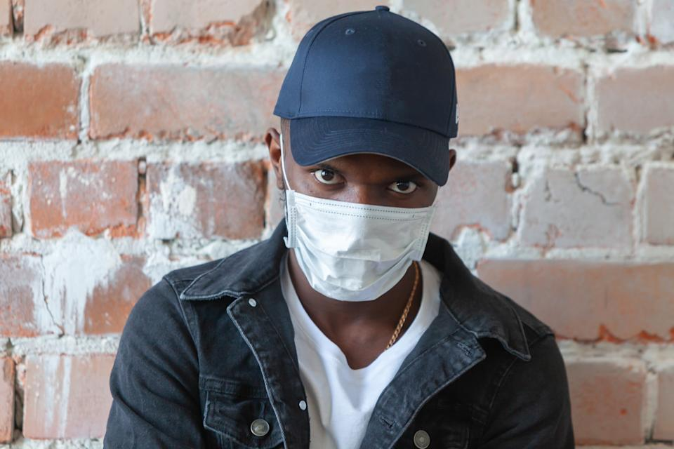 """""""The criminalization of blackness has spread during this pandemic,"""" notes one activist, explaining why men of color may fear that wearing masks for protection could bring them more harm than good. (Photo: Getty Images)"""