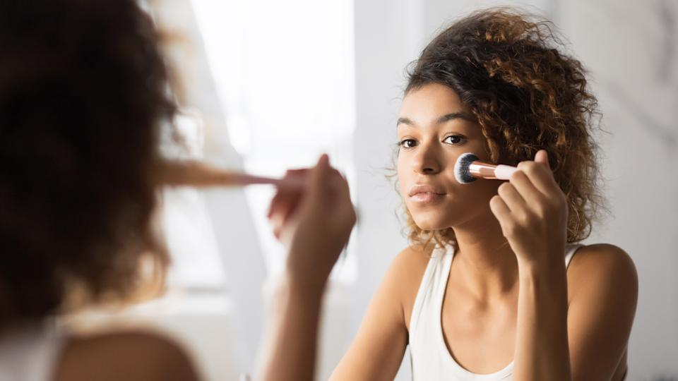 Makeup. Afro Young Woman Applying Face Powder With Cosmetic Brush Looking In Bathroom Mirror. Panorama, Selective Focus,