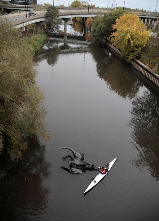 A replica equestrian statue of King Edward VII is nudged into position by Jon McCurley of art duo Life Of A Craphead, allowing it to float down the Don River at the start of a weekly performance in Toronto, Ontario, Canada October 29, 2017. REUTERS/Chris Helgren