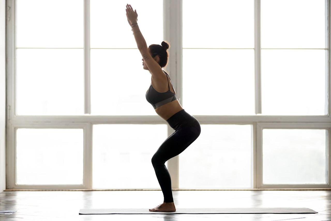 """<p>To do this move, you have to activate the largest muscles in the body-the <a href=""""https://www.prevention.com/fitness/a20491165/strengthen-your-hamstrings-butt-and-lower-back/"""" target=""""_blank"""">glutes</a>-which automatically burns lots of calories, says Kristin Lewis, instructor at <a href=""""http://www.y7-studio.com/"""" target=""""_blank"""">Y7 studio</a> in New York City. """"Chair pose is safe and easy for all yogis to perform,"""" she adds.</p><p><strong>How to: </strong>Begin by standing in mountain pose with your feet together and your hands at your sides. Then, bend your knees and send your hips back so your thighs are parallel to the floor, pressing your heels down to maintain stability. Your knees should go over your toes and your torso should have a slight forward lean. Push your shoulders down and back and then raise your arms above your head. </p>"""