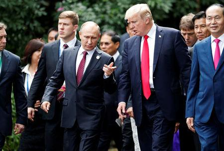 U.S. President Donald Trump and Russia's President Vladimir Putin talk during the family photo session at the APEC Summit in Danang, Vietnam