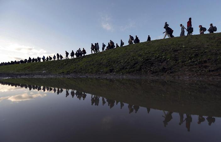 <p>Migrants make their way on foot on the outskirts of Brežice, Slovenia, Oct. 20, 2015. Slovenia's interior ministry raised the possibility on Tuesday of setting up physical barriers along its southeastern border if the numbers of migrants increased. <i>(Srdjan Zivulovic/Reuters)</i></p>