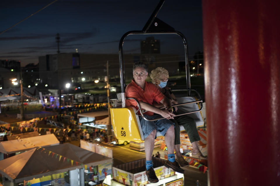 A couple, one wearing a mask, sit in a ride at the Mississippi State Fair in Jackson, Miss., on Wednesday, Oct. 7, 2020. (AP Photo/Wong Maye-E)