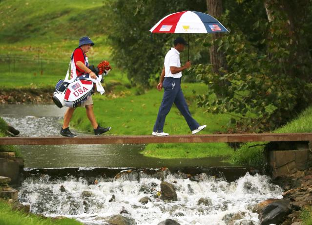 U.S. team member Tiger Woods walks across a creek bridge with his caddie Joe LaCava as he plays International team member Richard Sterne of South Africa during the Singles matches for the 2013 Presidents Cup golf tournament at Muirfield Village Golf Club in Dublin, Ohio October 6, 2013. REUTERS/Jeff Haynes (UNITED STATES - Tags: SPORT GOLF)