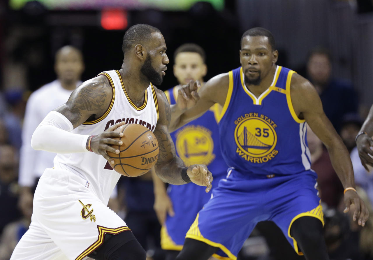FILE - In this Friday, June 9, 2017 file photo, Cleveland Cavaliers forward LeBron James (23) drives on Golden State Warriors forward Kevin Durant (35) during the second half of Game 4 of basketball's NBA Finals in Cleveland. The Golden State Warriors were the last team standing when the NBA season closed in June. Thanks to a preseason trip to China, they are one of the first teams to get going this season as the league gets up and rolling again. (AP Photo/Tony Dejak, File)