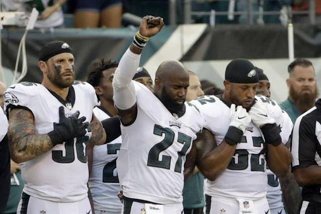Chris long, left, stands in support of Malcom Jenkins during his social protest. (AP)