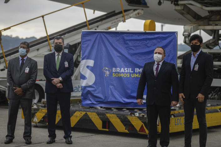 India's Ambassador to Brazil Suresh Reddy, left, Brazil's Foreign Minister Ernesto Araujo, second left, Brazil's Heath Minister Eduardo Pazuello, second from right, and Brazil's Communications Minister Fabio Faria stand in front of a container of vaccines for COVID-19, produced by Oxford/AstraZeneca, after it arrived from India at the international airport in Sao Paulo, Brazil, Friday, Jan. 22, 2021. (AP Photo/Marcelo Chello)