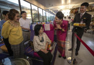 A flight attendant serves welcome drinks to customers in a flight-themed restaurant at the Thai Airways head office in Bangkok, Thailand on Oct. 3, 2020. The airline is selling time on its flight simulators to wannabe pilots while its catering division is serving meals in a flight-themed restaurant complete with airline seats and attentive cabin crew. The airline is trying to boost staff morale, polish its image and bring in a few pennies, even as it juggles preparing to resume international flights while devising a business reorganization plan. (AP Photo/Sakchai Lalit)