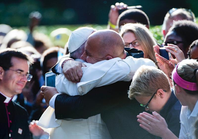Pope Francis gets a hug from a well-wisher at the Apostolic Nunciature on September 24, 2015 in Washington, DC (AFP Photo/Molly Riley)