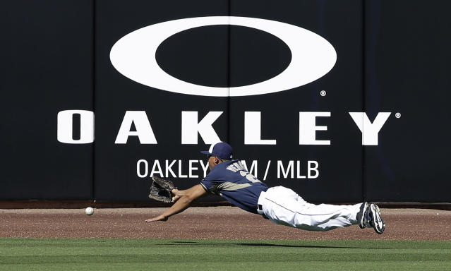 San Diego Padres center fielder Will Venable cannot make a catch on a ball hit by Cleveland Indians' Michael Brantley during the fifth inning of an exhibition spring training baseball game Saturday, March 8, 2014, in Peoria, Ariz. (AP Photo/Darron Cummings)