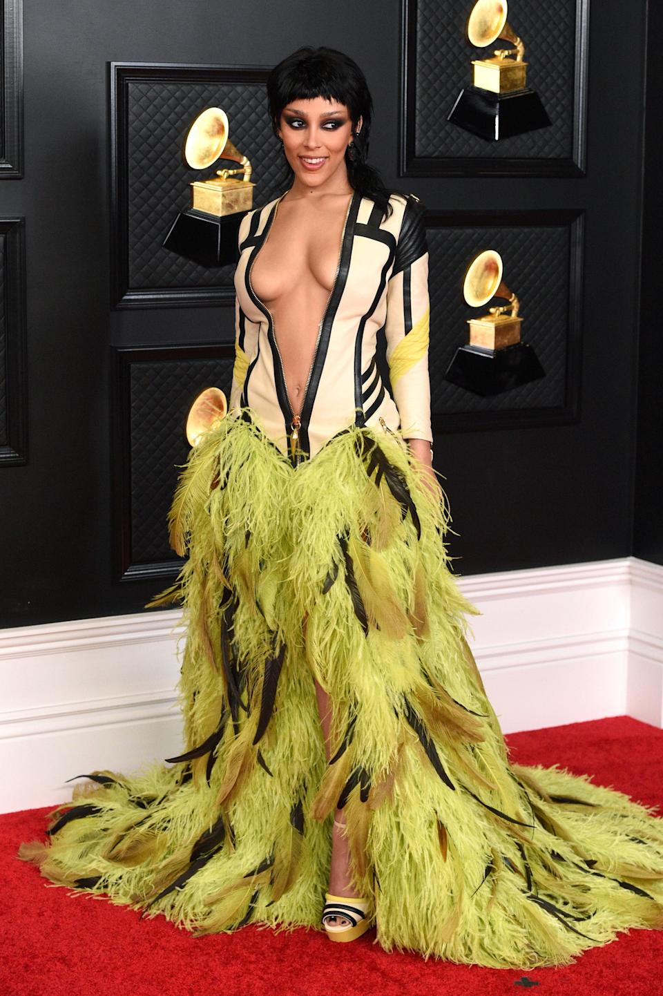 """<h2>Doja Cat in custom Roberto Cavalli</h2><br>Doja Cat wanted something that was """"out there"""" for the Grammys — and this feather <em>and</em> leather Roberto Cavalli look certainly fits the bill. <br>"""