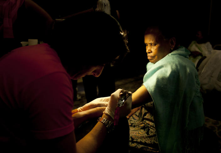 In this Monday, May 13, 2013 photo, Wassim Razzouk tattoos an Ethiopian Christian Orthodox pilgrim in a hotel in Jerusalem. The Razzouk family has been tattooing pilgrims with crosses and other religious symbols for hundreds of years, testament to the importance of the ancient ritual. While Catholics can get a written certificate of their pilgrimage to Jerusalem, Orthodox Christians opt for a tattoo, a permanent reminder of their visit. (AP Photo/Dusan Vranic)