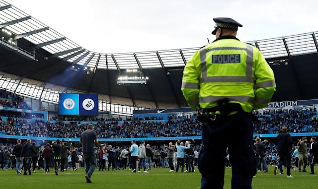 "Soccer Football - Premier League - Manchester City v Swansea City - Etihad Stadium, Manchester, Britain - April 22, 2018 Manchester City fans invade the pitch after the game as Police look on Action Images via Reuters/Lee Smith EDITORIAL USE ONLY. No use with unauthorized audio, video, data, fixture lists, club/league logos or ""live"" services. Online in-match use limited to 75 images, no video emulation. No use in betting, games or single club/league/player publications. Please contact your account representative for further details."