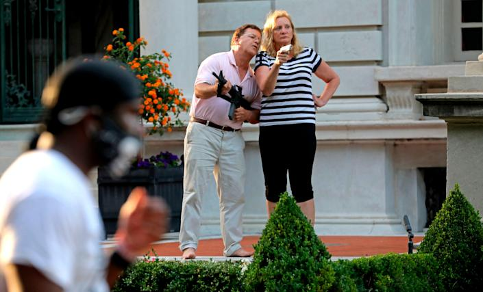 The governor of Missouri announced on Tuesday, 3 August, he had pardoned a St. Louis-area couple who went viral after pointing guns toward Black Lives Matter protestors on their way to a protest last summer.   ((Laurie Skrivan/St. Louis Post-Dispatch via AP, File))