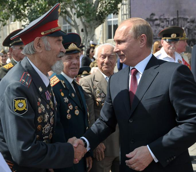 Russian President Vladimir Putin, right, greets World War II veterans before an opening ceremony of newly built fountain called Children Dancing in the southern Russian city of Volgograd, once known as Stalingrad, Friday, Aug. 23, 2013. The fountain is a replica of a fountain which miraculously survived in heavy bombing in Stalingrad in 1942. The original fountain survived until 1951. This year Russia celebrated the 70th anniversary of the end of one of modern warfare's bloodiest battles (in Stalingrad) that was turning point in World War II and led to the defeat of the Nazi Germany. (AP Photo/RIA-Novosti, Alexei Nikolsky, Presidential Press Service)