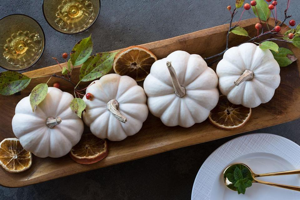 <p>Mini white pumpkins and orange slices add contrast to a long wooden tray—the perfect fall table setup.</p>