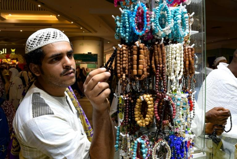 A pilgrim chooses a bracelet at a shop in the Saudi holy city of Mecca (AFP Photo/FETHI BELAID)