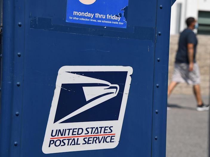<p>A man walks past a mail box outside a post office in Los Angeles, California on 17 August 2020</p> ((AFP via Getty Images))