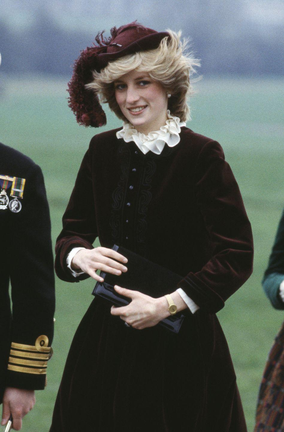 <p>In a velvet dress and matching hat in Birmingham. </p>