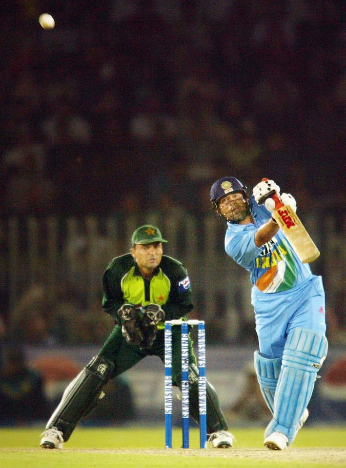 RAWALPINDI, PAKISTAN - MARCH 16:  Sachin Tendulkar (R) of India hits out during his innings of 141 as wicketkeeper Moin Khan of Pakistan watches during the second Pakistan v India one day international match played at Pindi Cricket Stadium March 16, 2004 in Rawalpindi, Pakistan. (Photo by Scott Barbour/Getty Images)
