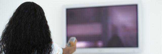 Rear view of a girl pointing a remote at a television.
