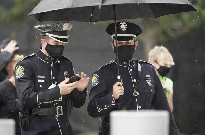Members of the Delray Beach Police force arrive in the rain for a memorial service for FBI Special Agent Laura Schwartzenberger, Saturday, Feb. 6, 2021, in Miami Gardens, Fla. Schwartzenberger and Special Agent Daniel Alfin were killed while serving a warrant this week in Sunrise, Fla. (AP Photo/Hans Deryk)