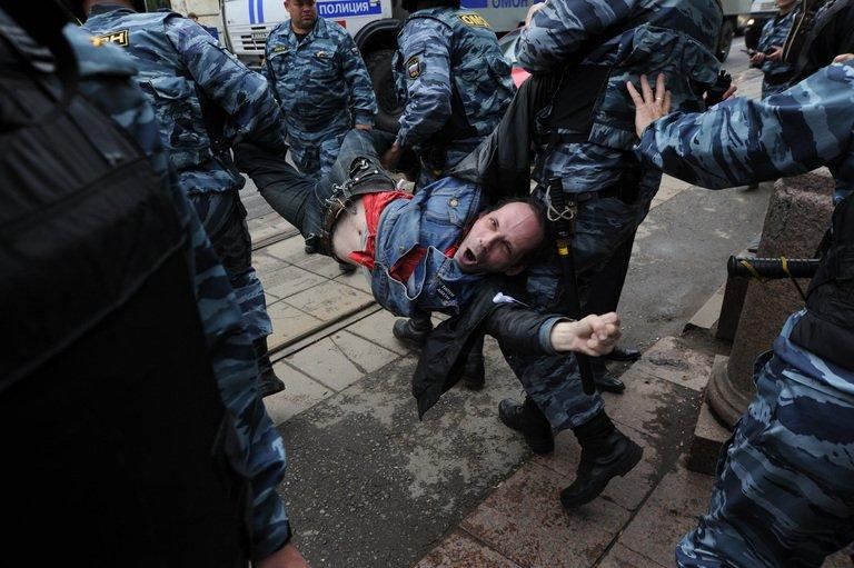 Police officers carry an anti-Putin protester, who was detained in central Moscow, on May 7, 2012. Thousands of Muscovites were due to rally Sunday in commemoration of a bloody protest one year ago in which more than 400 were detained after showing their frustration with Vladimir Putin's return to the presidency