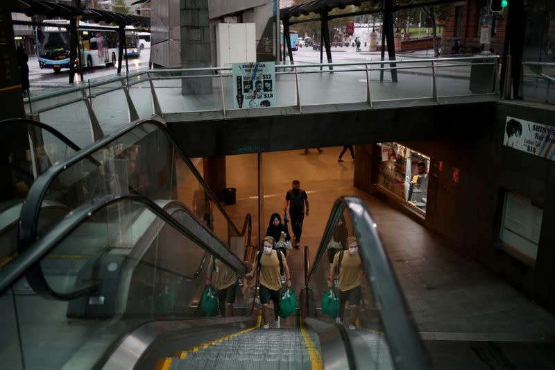 People wearing face masks use escalator at a city transit hub, as New South Wales begins shutting down non-essential businesses and moving toward harsh penalties to enforce self-isolation to avoid the spread of coronavirus disease (COVID-19), in Sydney
