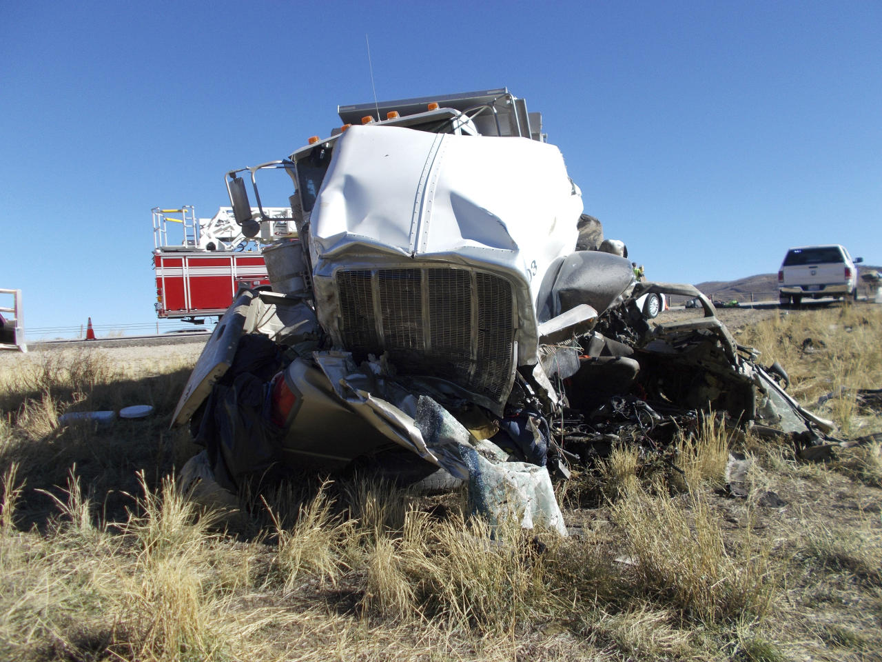 This Friday, Oct. 19, 2018 photo provided by the Utah Highway Patrol shows the scene of a head-on collision of a dump truck and a pickup on a state highway near Heber, Utah. State troopers say the dump truck crossed a highway median and collided with the pickup truck traveling in the opposite direction, killing all six men in the pickup in an accident authorities suspect may was caused by alcohol and prescription drugs. The Utah Highway Patrol said Saturday its officers found prescription pills and open containers of alcohol inside the dump truck. (Utah Highway Patrol via AP)