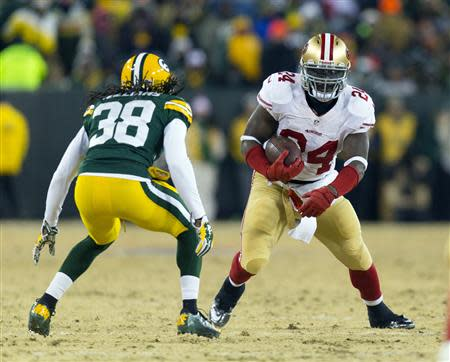Jan 5, 2014; Green Bay, WI, USA; San Francisco 49ers running back Anthony Dixon (24) rushes with the football as Green Bay Packers cornerback Tramon Williams (38) defends during the third quarter of the 2013 NFC wild card playoff football game at Lambeau Field. Mandatory Credit: Jeff Hanisch-USA TODAY Sports