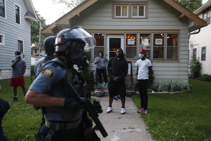 """Bystanders watch as police walk down a street in St. Paul, Minn. Protests over the death of George Floyd, a black man who died in police custody, broke out in Minneapolis for a third straight night. <span class=""""copyright"""">(John Minchillo / Associated Press)</span>"""