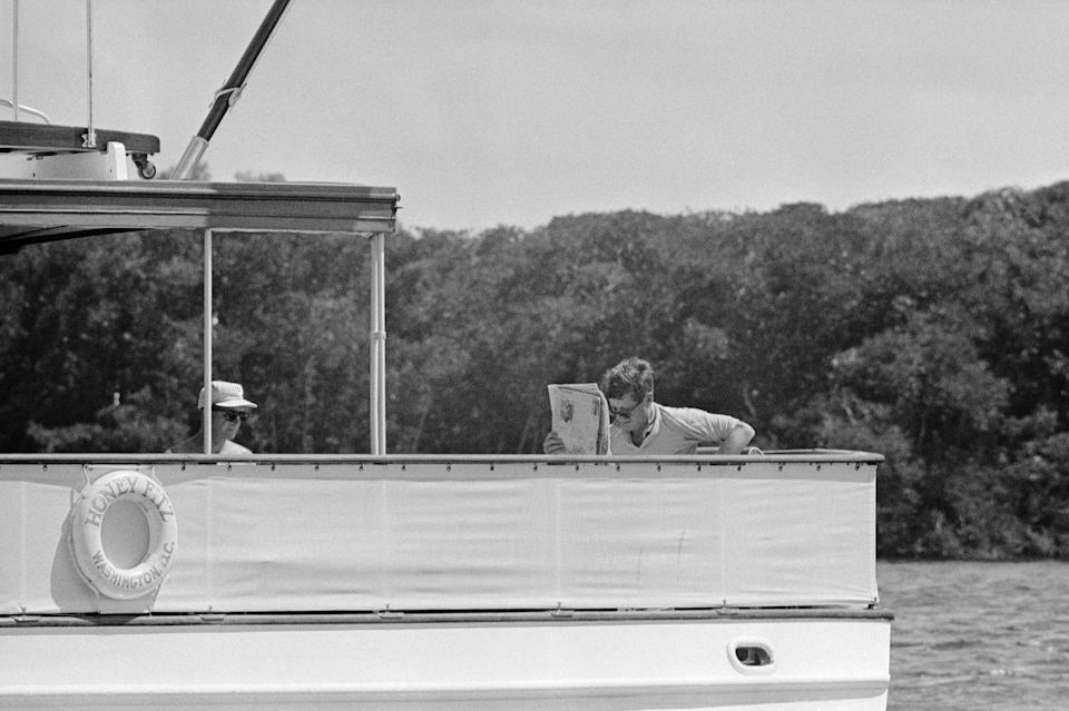 <p>John F. Kennedy relaxes as he reads the paper onboard his boat, Honey Fitz, in 1963. The President was spending time in Palm Beach, Florida, before traveling to Costa Rica for work. </p>