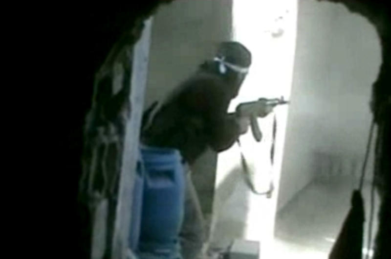 This image made from citizen journalist video posted by the Shaam News Network, which is consistent with other AP reporting, a Syrian rebel fires an automatic weapon in the Daraya district of Damascus, Syria, Monday, Oct. 28, 2013. The fighting coincided with the first visit to Syria by the U.N.-Arab League envoy Lakhdar Brahimi in almost a year. (AP Photo/Shaam News Network via AP video)
