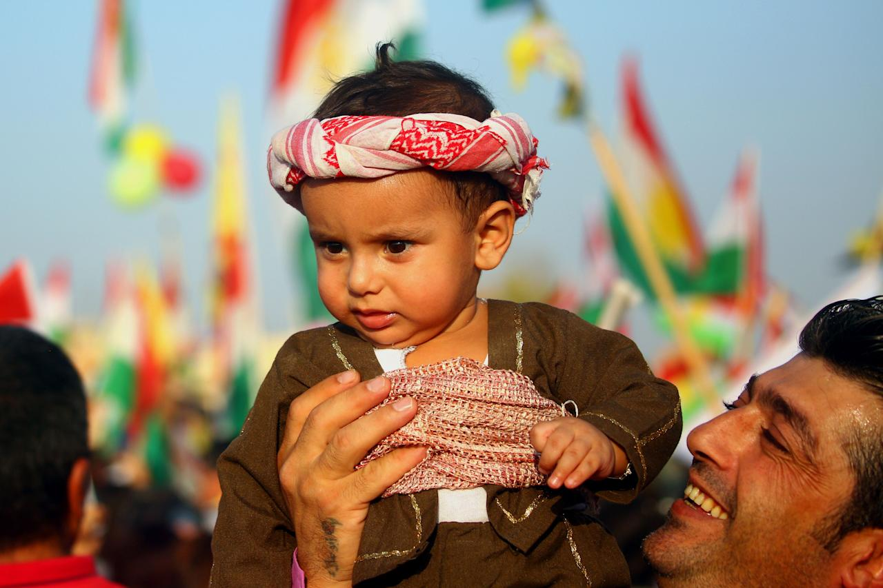 <p>A Syrian Kurdish man holds a child dressed in a traditional outfit as he takes part in a rally in the northeastern Syrian city of Qamishli on Sept. 15, 2017, in support of an independence referendum in Arbil. (Photo: Safin Hamed/AFP/Getty Images) </p>