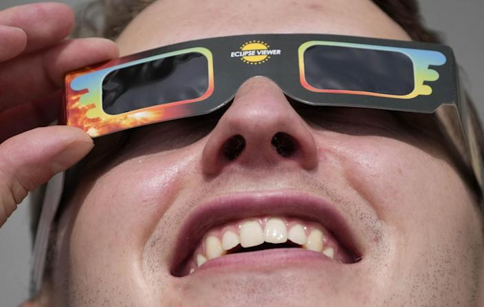A man wears special glasses to watch the partial solar eclipse in Trafalgar Square in London.