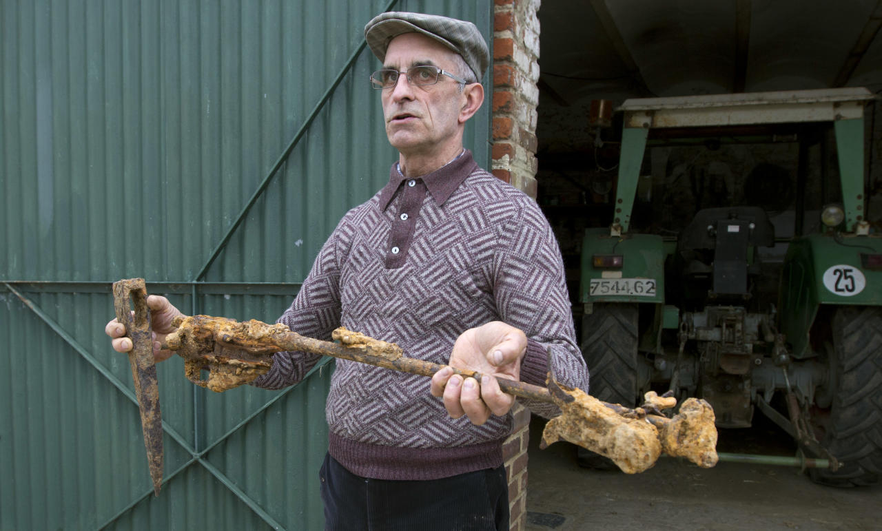 Farmer Didier Guerle shows a rusted and deteriorated rifle and pickaxe which he found in a field in 2009 near the site of where he also located the bodies of two British World War One soldiers in Bullecourt, France on Monday April 22, 2013. Almost 100 years after they were killed in action, Lieutenant John Harold Pritchard and Private Christopher Douglas Elphick will re-interred with full military honors in the H.A.C Cemetery at Ecoust-St. Mein, France, on Tuesday, April 23, 2013. (AP Photo/Virginia Mayo)