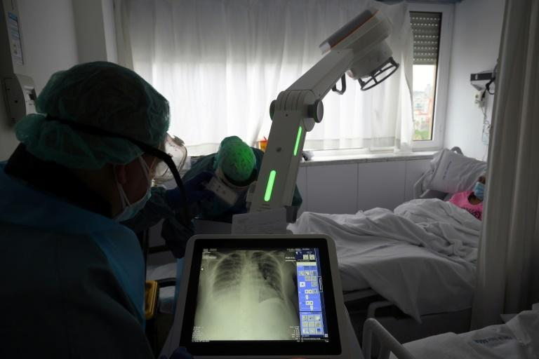 A healthcare worker checks a patient's X-ray at the Covid-19 wing of the Hospital Del Mar in Barcelona. Four of the hospital's 12 floors are devoted to coronavirus patients