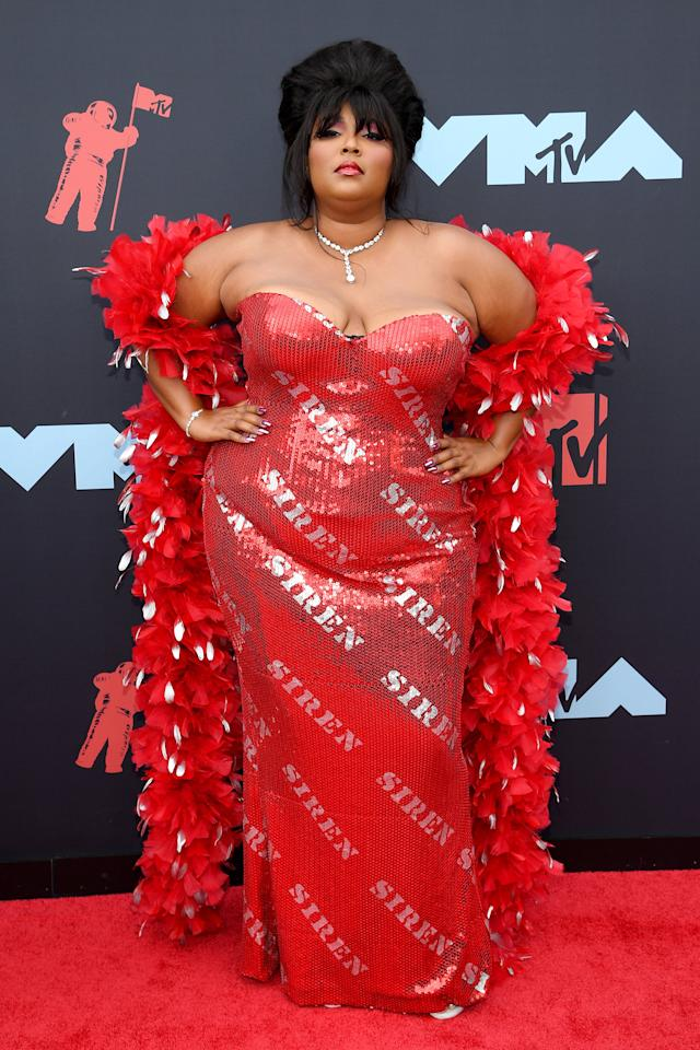 <p>Lizzo heated up the red carpet in an off-the-shoulder red dress complete with a feather boa.</p>