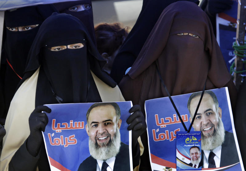 FILE - In this Friday, April 20, 2012 file photo, Egyptian women hold posters supporting Muslim cleric Hazem Abu Ismail, an ultraconservative Salafi preacher who was disqualified from running for the presidential elections on technical grounds, during a demonstration at Tahrir Square, in Cairo, Egypt. Radical Islamists in Egypt dream of turning the most populous Arab country into a religious state. With their scourge Hosni Mubarak out of the way, the most extreme fringe of Islamists is flexing its muscles, adding a potentially destabilizing layer to Egypt's multiple political troubles ahead of presidential elections. (AP Photo/Amr Nabil, File)