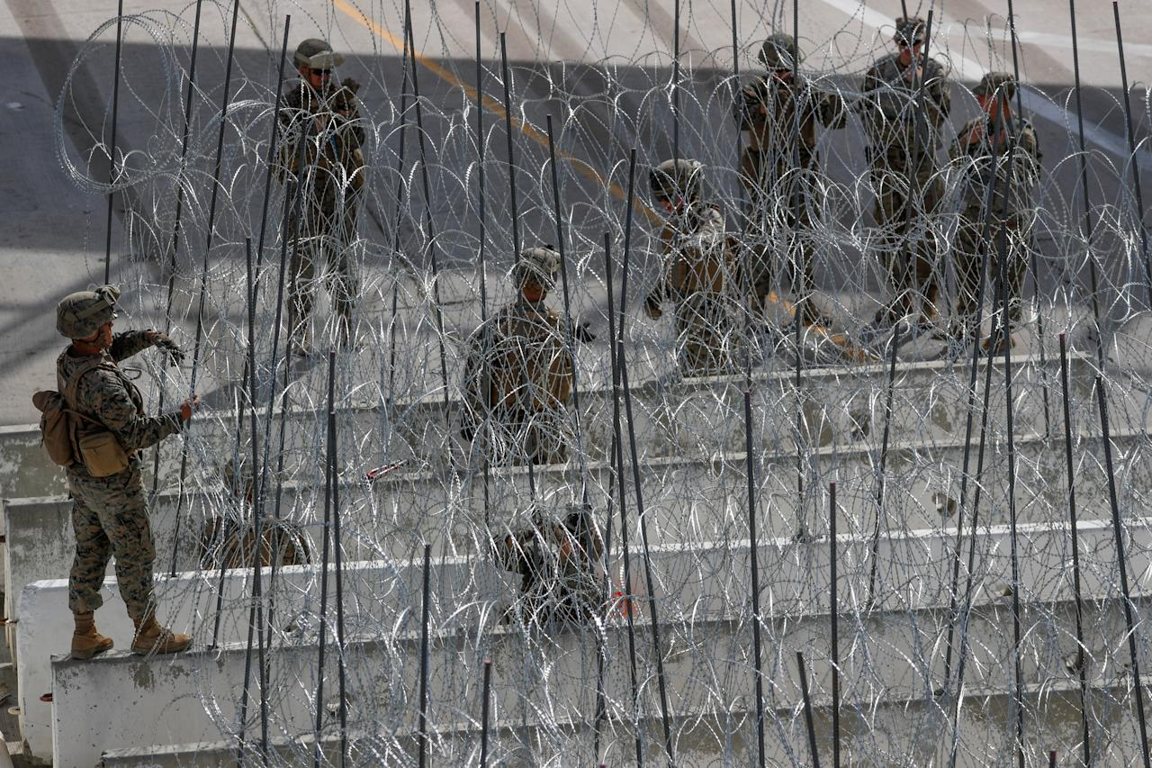 <p>U.S. Marines help to build a concertina wire barricade at the U.S. Mexico border in preparation for the arrival of a caravan of migrants at the San Ysidro border crossing in San Diego, Calif., Nov. 13, 2018. (Photo: Mike Blake/Reuters) </p>