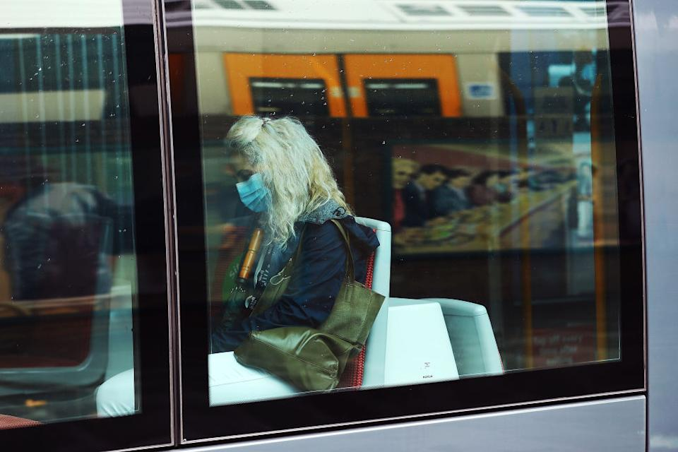 A commuter wearing a face mask travels on the light rail at Central Station in Sydney, Australia.